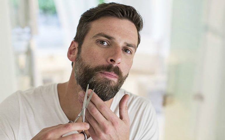 man trimming beard scissors grooming