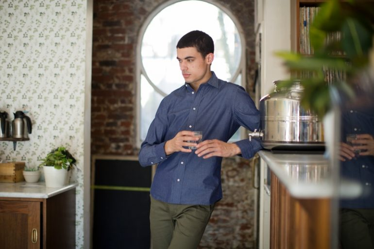man wearing green chinos and a navy shirt