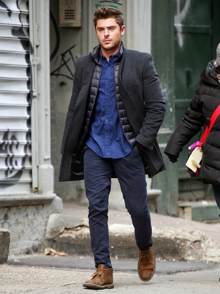 mens street style zac efron black coat blue shirt blue chinos brown desert boots