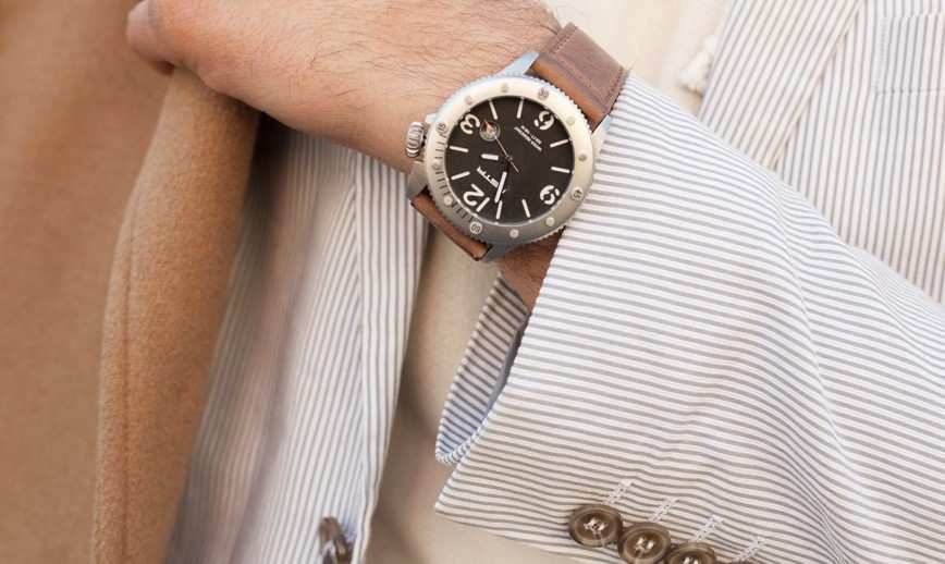 mens watch with brown strap and striped suit