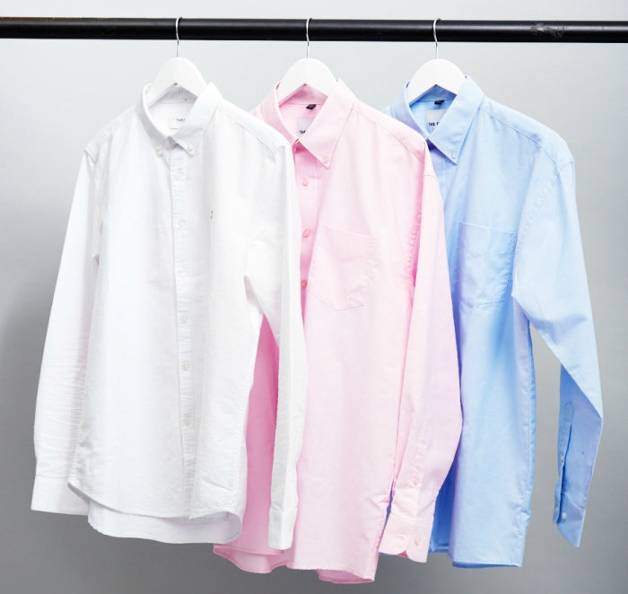 white shirt pink shirt blue shirt on a rail
