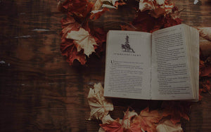 open harry potter book surrounded by orange and yellow autumn leaves on a brown desk