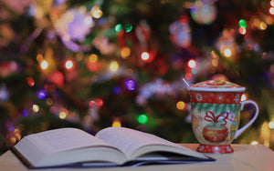an open book next to a holiday themed mug and in the background there's a christmas tree decorated with lights