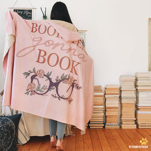 pink booksters gonna book hooded blanket for readers in front of a pile of books organized on the floor