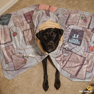 a black labrador wearing a blanket with a button made for readers