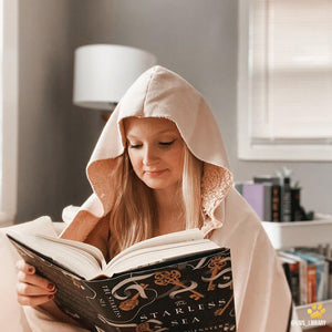 bookstagrammer wearing the hood of an emposia blanket while reading a book