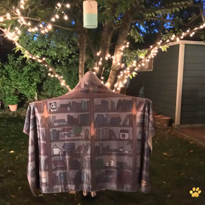 emposia shelfie bookish hooded blanket worn outdoors under fairy lights