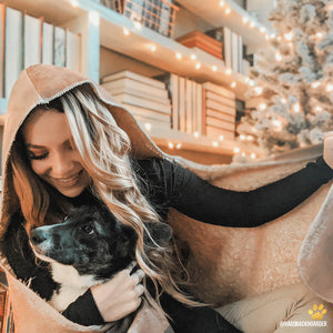 a book lover girl wearing a hooded blanket and holding her dog with a christmas tree and lights in the background