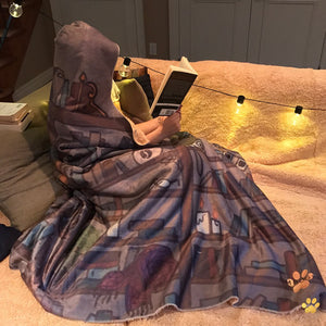 bookstagrammer wearing her cozy emposia hooded blanket while reading a book in her nook