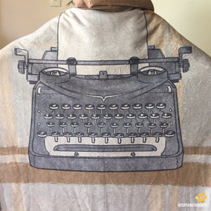 a typewriter design on an emposia hooded blanket made for book lovers