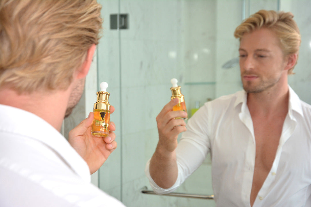 Fabio Grangeon holding a bottle of Arganne 100% Pure Argan Oil in the bathroom.