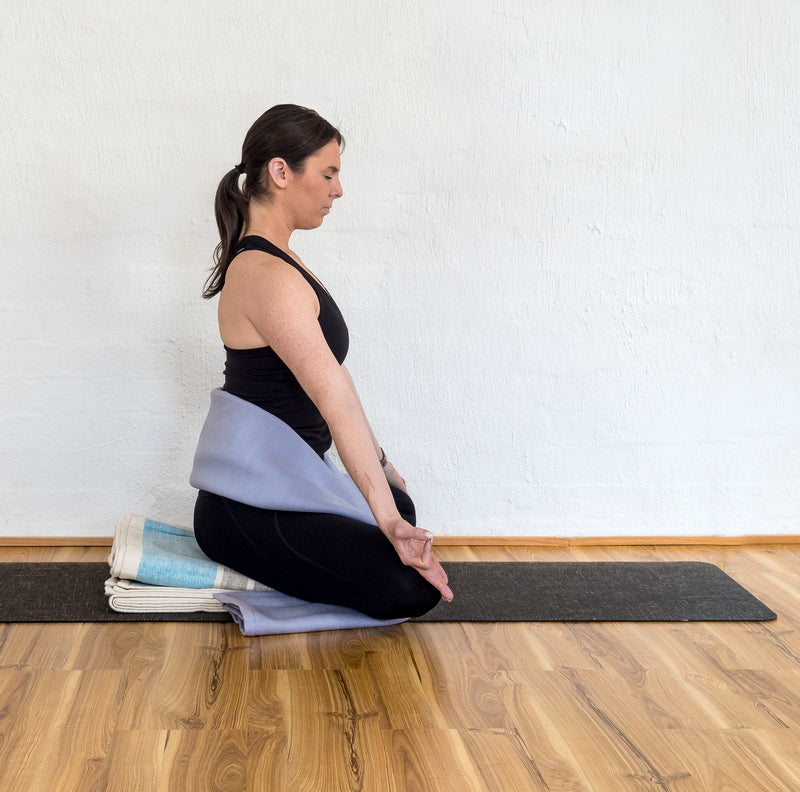 Wrapping a long-fold blanket around your lower back and torso, like a firm, wide belt.