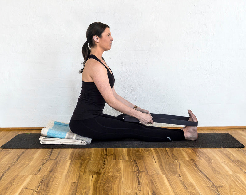 Seated forward bend using yoga blanket and yoga strap