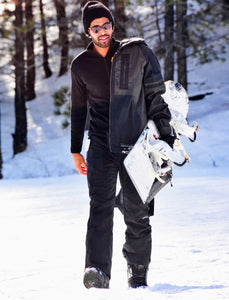 man carrying snowboard wearing alpaca base layer
