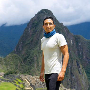 Man wears Arms of Andes White 100% Royal Alpaca Wool Crew Neck Shirt in front of Machu Picchu