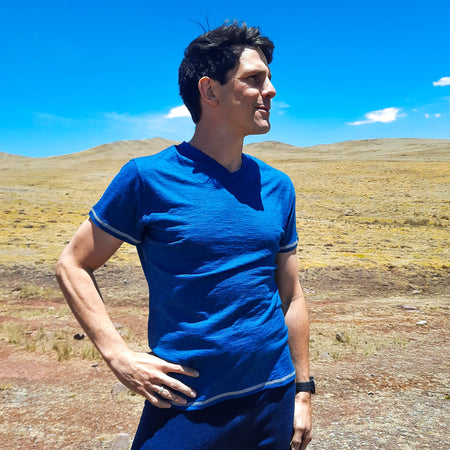 Man hiking in lilac alpaca wool shirt in front of the hills