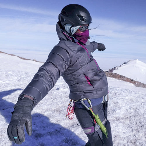 Woman wearing layered clothing on the peak of a snowy mountain