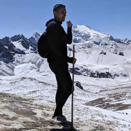 Man wearing alpaca wool base layer and wool hiking pants with a snowy mountain background