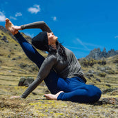 Woman practicing yoga in naturally dyed alpaca wool outdoor clothing