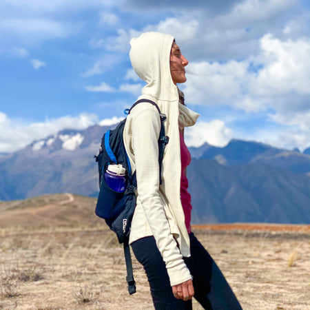 Woman wearing white alpaca midlayer hoodie in the mountains
