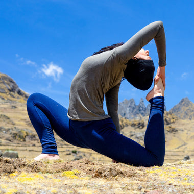 Woman stretching in alpaca wool tights on a mountain top