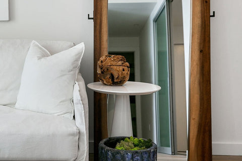 This smoky walnut floor mirror makes a dramatic impression. The mirror itself is flanked by two panels of live-edge wood, a sculptural detail that ensures this piece stands as a work of art you can use and appreciate every day. Convenient hooks provide a place to hang everyday essentials like handbags.