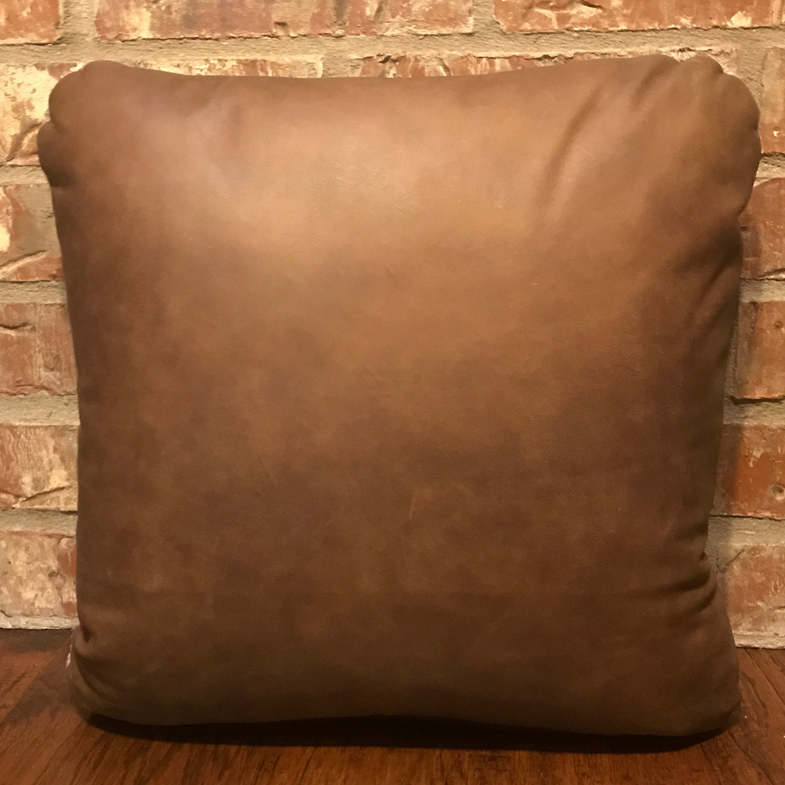 "This 16"" x 16"" pillow is medium brindle cowhide on one side and two-tone tan leather on the other side."