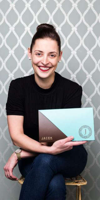 A portrait of Jacqueline Jacek. She is seated in front of a elegant wallpapered wall, and is smiling while holding a 24-pc chocolate box.