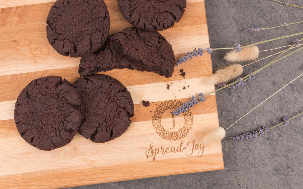 """Soft and chewy Peanut Butter Chocolate Cookies on a wooden board with the JACEK logo and the slogan """"spread joy"""" underneath."""