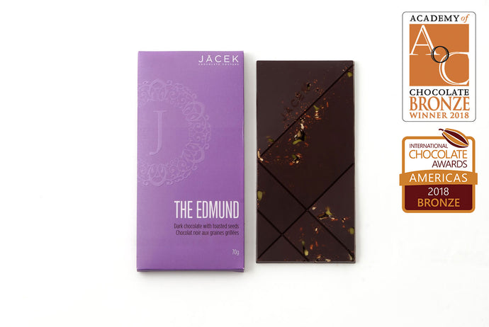 Pictured beside its purple box, The Edmund Bar is solid dark chocolate with toasted seeds peeking out.