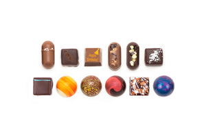 "12-piece collection featuring one solid milk chocolate with the words ""Happy Birthday"" on it. The text is in orange, with an illustration of a party hat in the top corner."