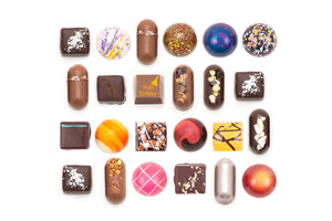 "24-piece collection featuring one solid milk chocolate with the words ""Happy Birthday"" on it. The text is in orange, with an illustration of a party hat in the top corner."