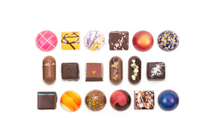 "18-piece collection featuring one solid milk chocolate with the words ""Love You"" on it. The text is in dark pink, with the letter ""o"" in the word ""you"" as a yellow and pink heart."