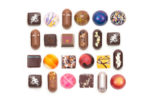 "24-piece collection featuring one solid milk chocolate with the words ""Love You"" on it. The text is in dark pink, with the letter ""o"" in the word ""you"" as a yellow and pink heart."