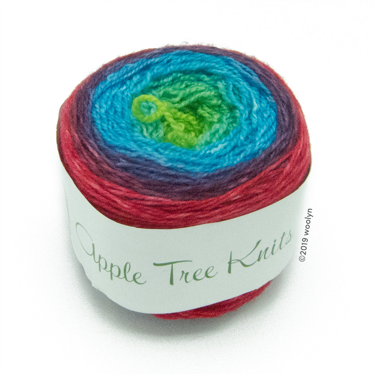 A wound cake of hand dyed fingering weight yarn from Apple Tree Knits.  Yarn is a gradient from red to purple to turquoise to bright green.