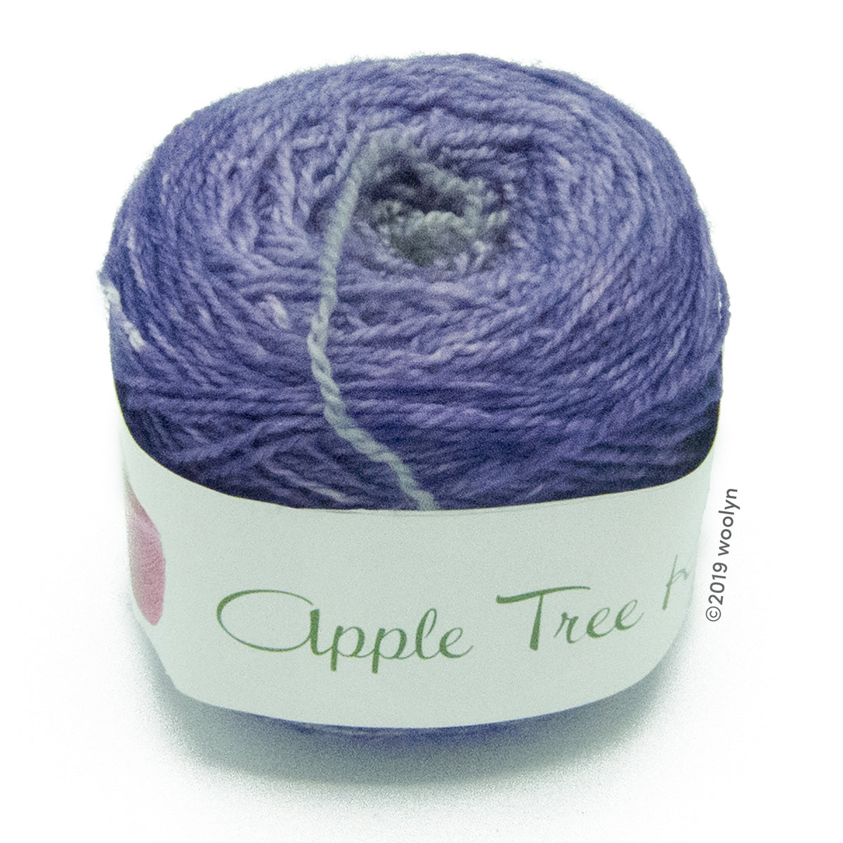 A wound cake of hand dyed fingering weight yarn from Apple Tree Knits..  Yarn is a gradient from light grey to medium purple.