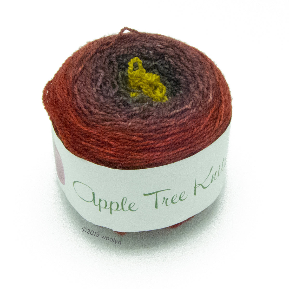 A wound cake of hand dyed fingering weight yarn from Apple Tree Knits..  Yarn is a gradient from reddish brown to dark brown to bright acid green.