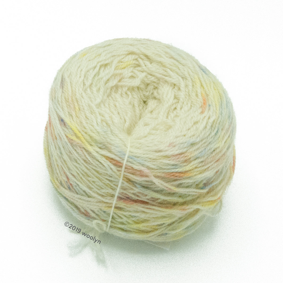 A wound cake of hand dyed fingering weight yarn from Apple Tree Knits..  Yarn is a gradient from white to pastel speckles.