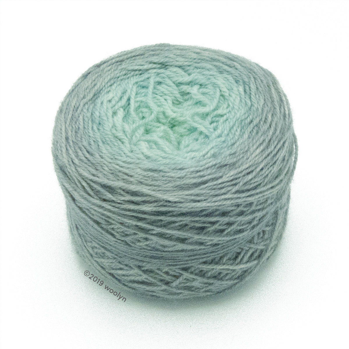 A wound cake of hand dyed fingering weight yarn from Apple Tree Knits..  Yarn is a gradient from medium grey to light pale blue.