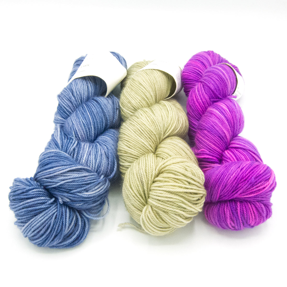 Three skeins of hand dyed yarn.  Medium purply blue, light yellow and bright pink.