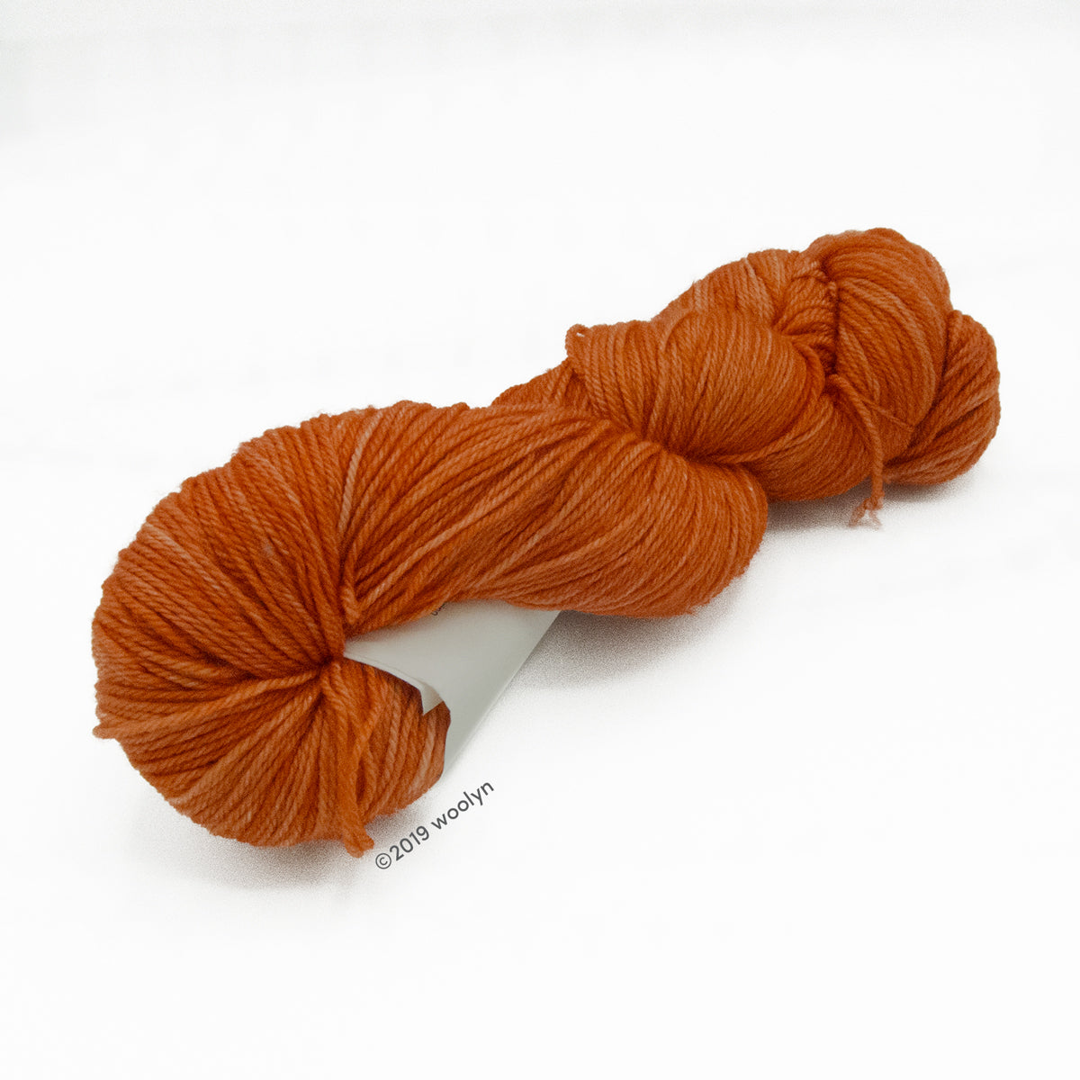 Hand dyed dark brownish orange yarn twisted into a skein.
