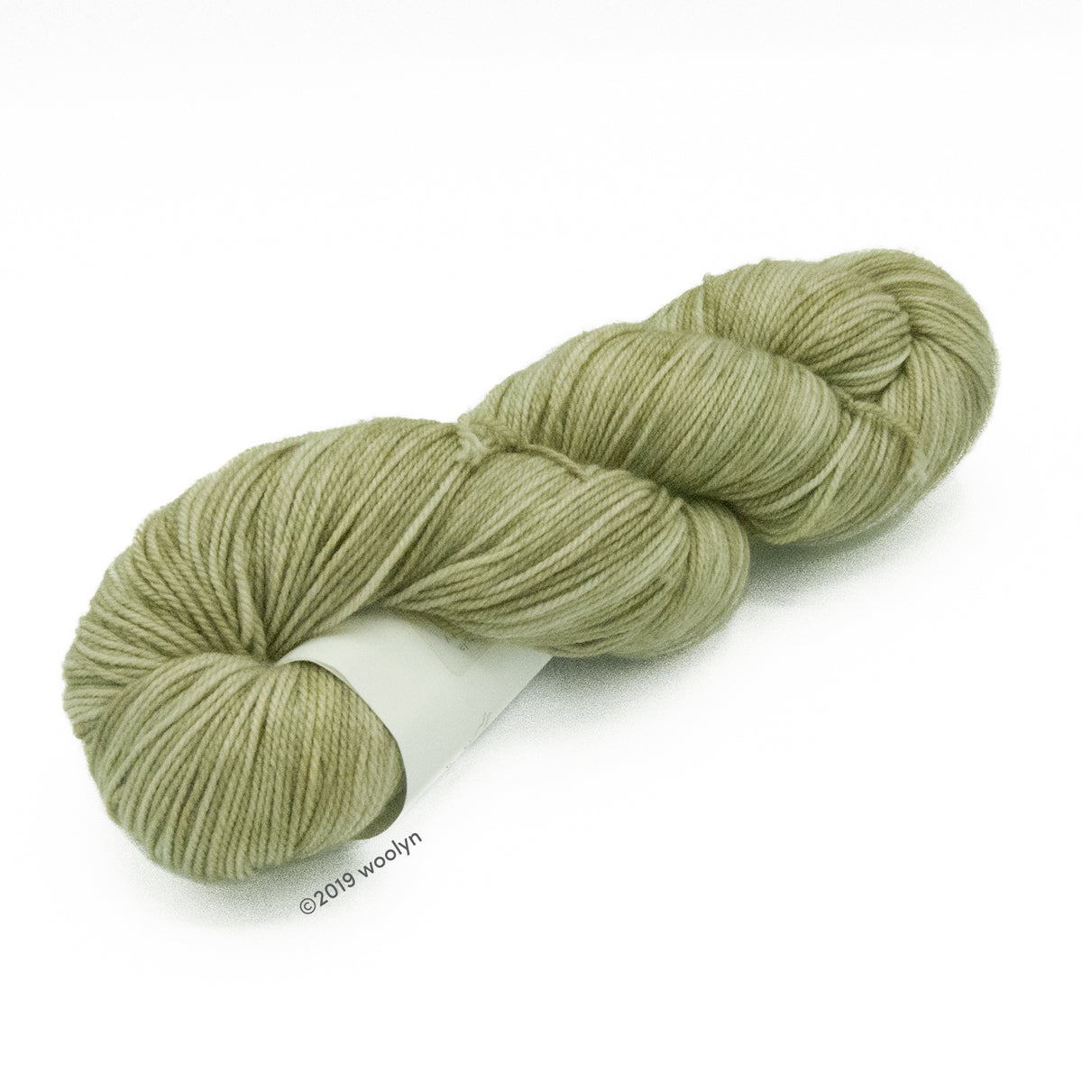 Hand dyed  fingering weight yarn in pale greyish green  tonal shades twisted into a skein.