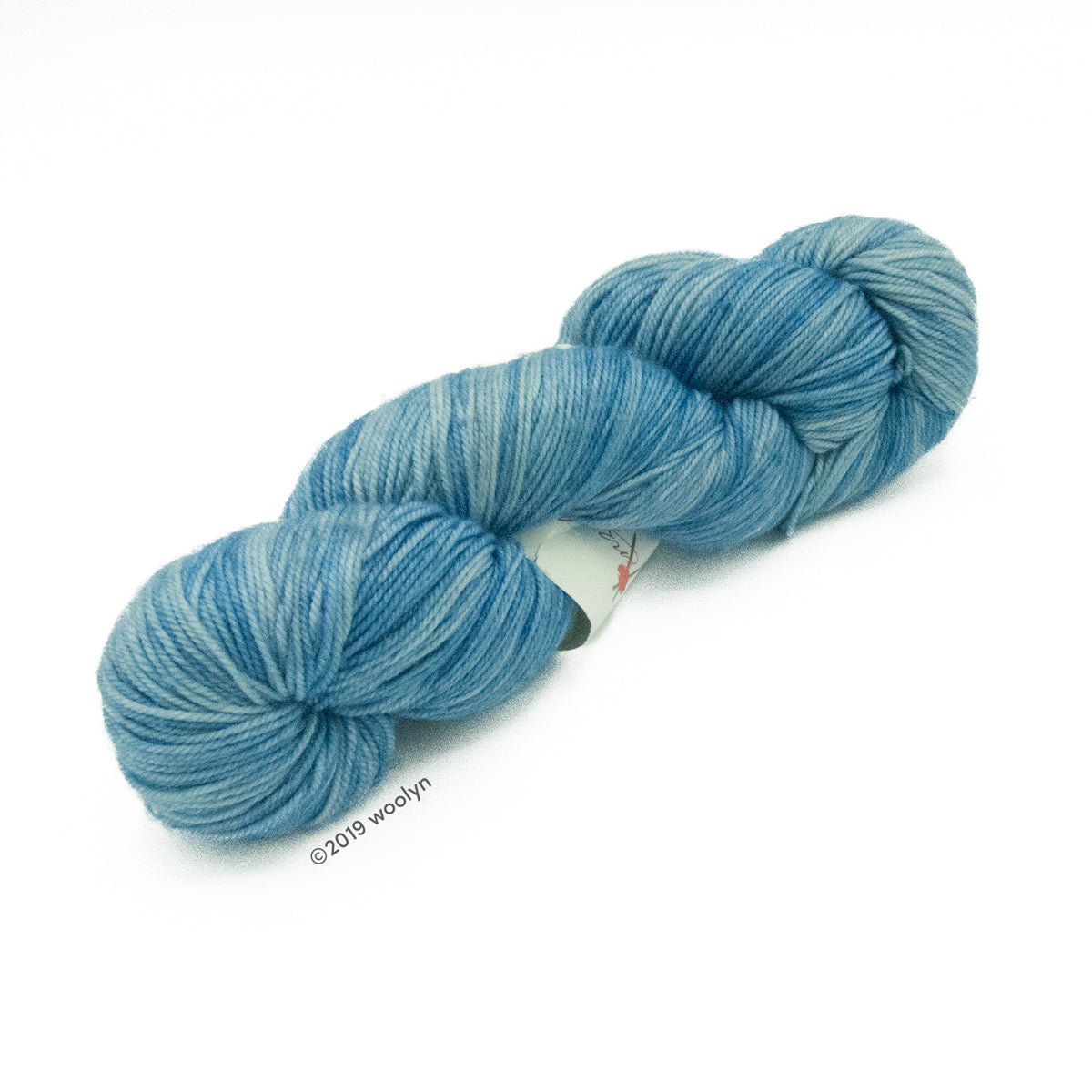 Hand dyed  fingering weight yarn in light blue tonal shades twisted into a skein.