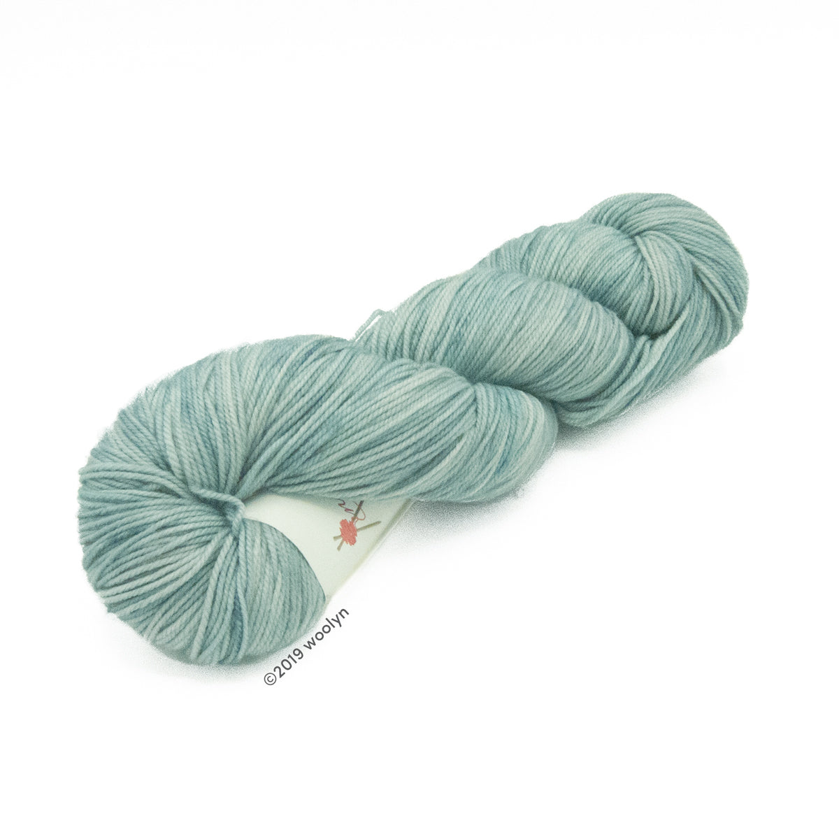 Hand dyed  fingering weight yarn in cool light green tonal shades twisted into a skein.