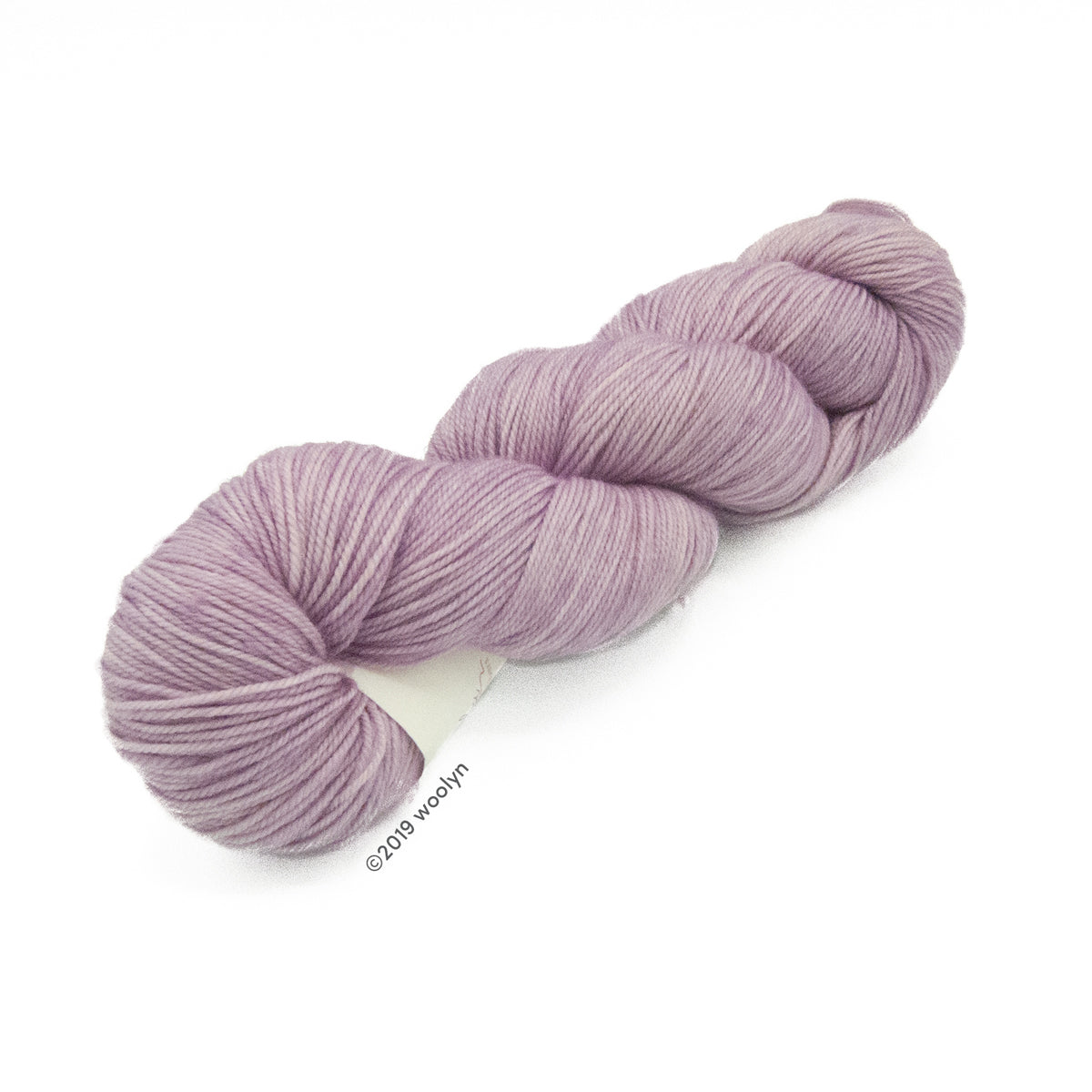 Hand dyed fingering weight yarn in pale lavender pink tonal shades twisted into a skein.
