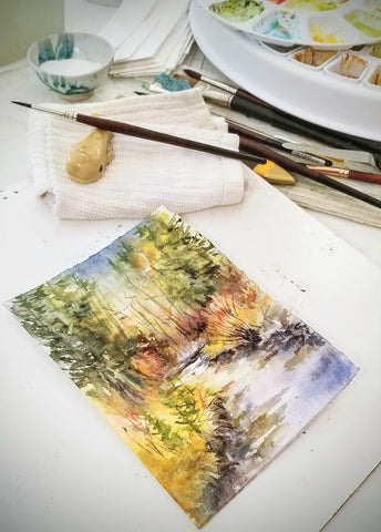 Watercolor painting of a mountain stream in progress; snapshot of the art studio workspace.