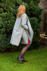 Unique look with our open sided  black and white check coat with contrast color red lining and  fringed hem