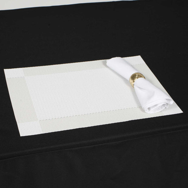 White placemat with white napkin on black tablecloth