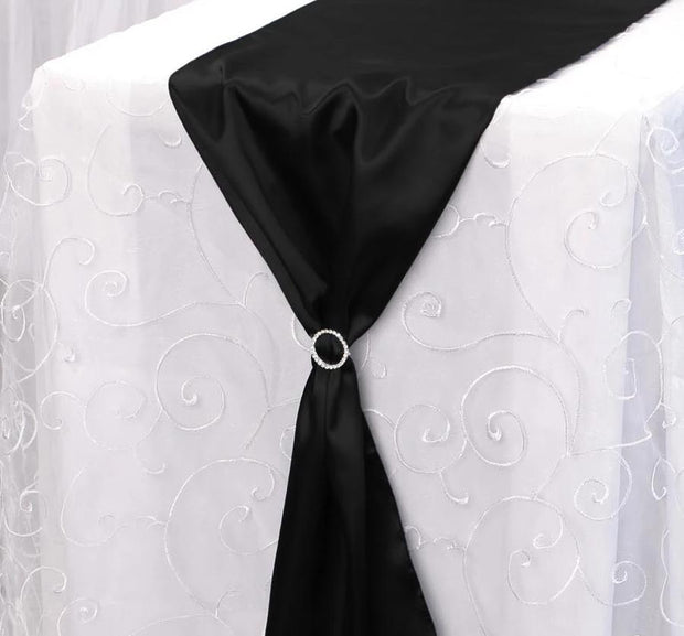 Sparkling buckle with black satin table runner