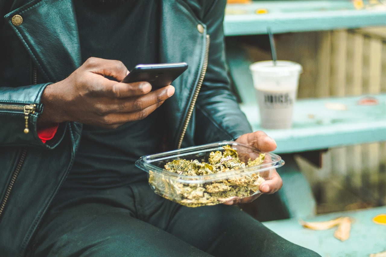 Hip man in black leather jacket holding container of Chicago Kale Chips in one hand while looking at his phone in his other.
